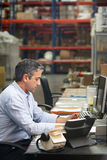Manager Working At Desk In Warehouse. Taking Notes royalty free stock photos