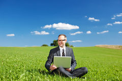 Manager working outdoors on his laptop. Sitting on the grass in a field under a sunny blue sky in open countryside Stock Photography