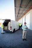 Manager working on tablet and warehouse workers loading the cardboard boxes Stock Photo