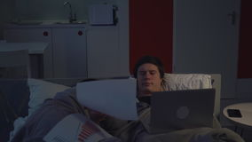 Manager works at night at home. Businessman working in bed. Young man using laptop lying near sleeping girlfriend stock video footage