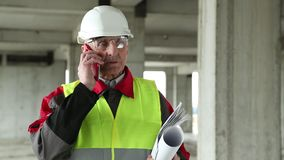 Manager of the works with red smartphone on the construction site