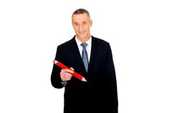 Manager writing with an oversized red pencil Stock Images
