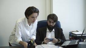 Manageress показывая документы к ее боссу в офисе Вождь играет по его телефону во время встречи сток-видео