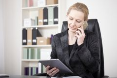Manageress Holding a Tablet While Calling on Phone. Close up Businesswoman in Black Suit Holding a Tablet Device While Calling to Someone on Mobile Phone Royalty Free Stock Photography