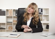 Manageress pointing to her watch Stock Photo