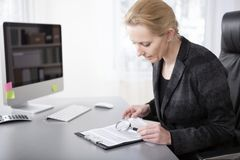 Manageress Reading Details Using Magnifying Glass Stock Photos