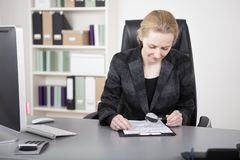 Manageress Reading Documents with Magnifying Glass Royalty Free Stock Photography