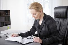 Manageress Scanning Papers with Magnifying Glass Royalty Free Stock Photography