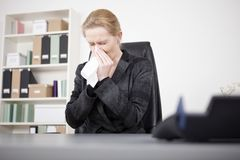 Manageress Sneezing with Eyes Closed at her Office Stock Photography