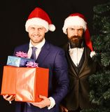 Managers with beards get ready for Christmas. Businessmen with happy faces hold Christmas tree and presents. Men in smart suits and Santa hats on brown royalty free stock photo