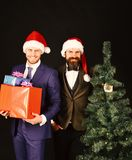 Managers with beards get ready for Christmas. Men in suits. Managers with beards get ready for Christmas. Men in classic suits and Santa hats on brown background royalty free stock images
