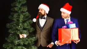 Managers with beards get ready for Christmas. Men in suits. Managers with beards get ready for Christmas. Men in smart suits and Santa hats on brown background royalty free stock photography