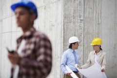 Managers With Blueprint And Worker In Foreground Royalty Free Stock Image