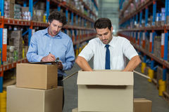 Managers are checking some cardboard boxes. In a warehouse stock photo