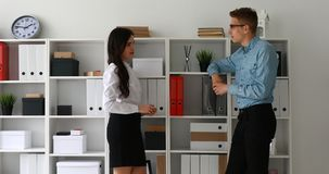Managers communicate standing near cabinet with folders.