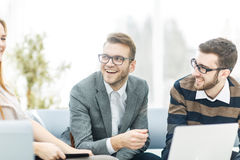 Managers of the company and the client, discussing the terms of the new contract and look at the laptop screen with the Royalty Free Stock Photos