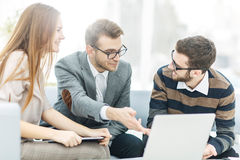 Managers of the company and the client, discussing the terms of the new contract and look at the laptop screen with the Royalty Free Stock Images