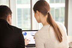 Managers die project infographic stats bij laptop het scherm, r analyseren royalty-vrije stock afbeeldingen