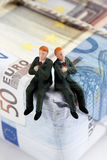 Managers figurines sitting on package of euro notes Stock Photos