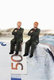 Managers figurines sitting on package of euro notes Royalty Free Stock Images