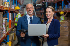 Managers are holding a laptop and looking the camera. In a warehouse Royalty Free Stock Images