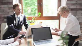 Colleagues of the case man and woman sit in the office at the desk after a business meeting. Managers of a large company are preparing for a business meeting stock footage