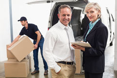 Managers smiling at camera with delivery driver behind Royalty Free Stock Image