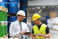 Managers and workers in the logistics industry talk about working with chemicals in the warehouse royalty free stock images