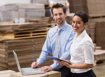 Managers working on laptop while smiling at camera Stock Image