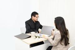 Managerzakenman die met onderneemster op bureau spreken royalty-vrije stock afbeelding