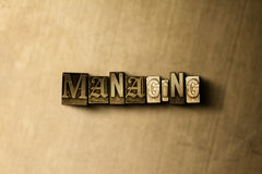 MANAGING - close-up of grungy vintage typeset word on metal backdrop Royalty Free Stock Photos