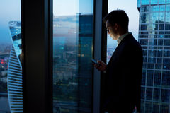 Managing director dressed in elegant clothes using mobile phone while resting after late briefing in the nighttime. Young smart male entrepreneur read text royalty free stock photos