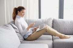 Managing her business from home. Home office. Full length shot of an attracitve woman using mobile phone and laptop while working from home Royalty Free Stock Photo