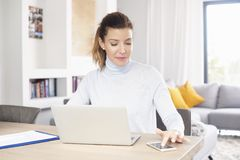 Managing my business from home. A beautiful middle aged woman using laptop and mobile phone while sitting at desk and working from home. Home office Stock Photography