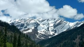 Manali. The beautiful snow covers the mountain with cloud as crown on its top in Manali royalty free stock photo