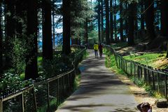 Manali, India, April 2018 - Twee niet geïdentificeerde toeristen die over de weg in Hidimba-tempel, Manali, India lopen Dit is ee royalty-vrije stock afbeelding