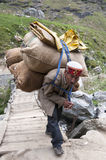 MANALI, INDIA - SEPTEMBER 09 2014: Old man carrying bags with sheeps wool crossing the bridge on September 9th 2014 in Manali, Ind Royalty Free Stock Photos