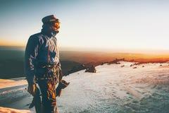 Manalpinisten hälsar gryningen i bergklättring Fotografering för Bildbyråer