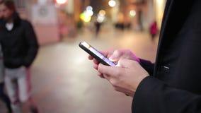 Mananseende i en gata och smsa för stad som är snabba på den smarta telefonen