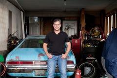 Mananseende i hans belamrade garage bredvid en gammal bil Arkivbilder