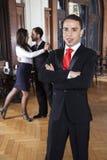 Mananseende med korsade armar medan dansare som utför tango Arkivbilder
