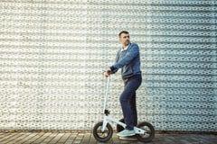 Mananseende med sparkcykeln mot bakgrunden av stålfasaden fotografering för bildbyråer