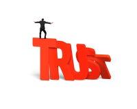Mananseende som balanserar på att falla för förtroendeorddomino Royaltyfri Fotografi