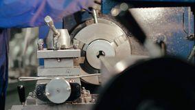 Mananställd som arbetar på den moderna roterande drejbänk- och metalworkingmaskinen stock video