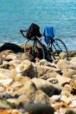 Manapany,法国- 2018年9月27日:在石海滩停放的自行车,当所有者采取游泳时 免版税库存图片