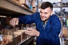 Manarbetare som går till och med detaljer för sanitär teknik i worksho Royaltyfri Bild