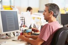 Manarbete på skrivbordet i upptaget idérikt kontor royaltyfri foto
