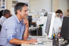 Manarbete på skrivbordet i upptaget idérikt kontor Arkivbild
