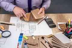 Manarkitekten drar ett husplan med färgpaletten för möblemang, Arkivfoto
