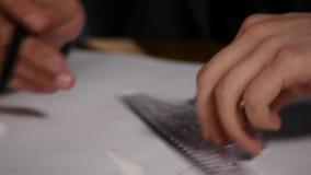 Manarkitekten drar ett plan, grafen, designen, geometriska former vid blyertspennan på det stora arket av papper på kontorsskrivb lager videofilmer